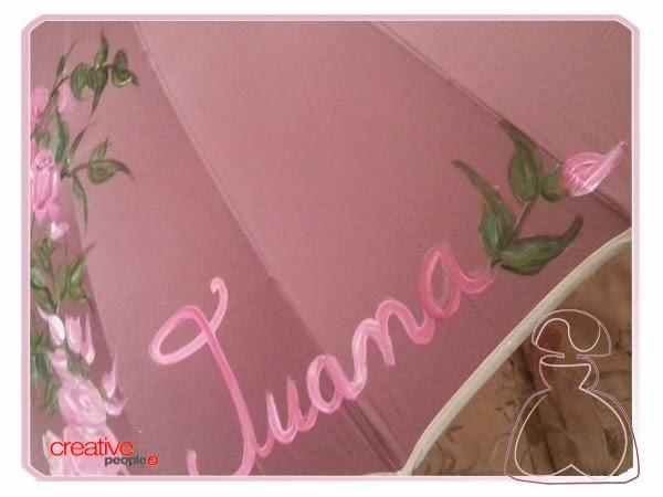 Pequeño capullo de rosa que rodea al nombre en el paraguas pintado a mano por Sylvia Lopez Morant.