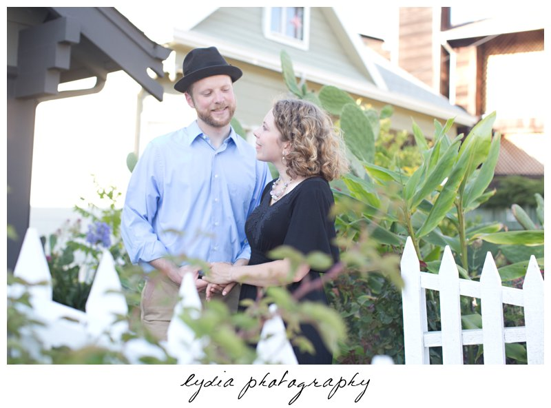 Bride and groom in a fenced area with bushes at lifestyle engagement portraits in the Bay Area of California