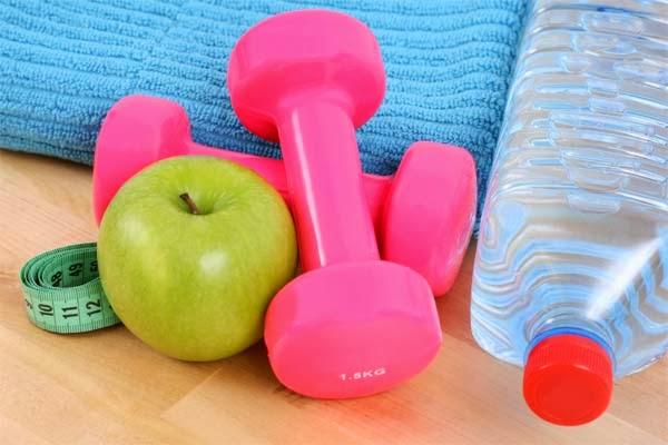 Pesos, garrafa de água e maçã pra lanche na academia