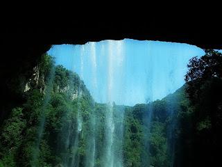 Caverna Salto Ventoso, Farroupilha. Queda d'água emoldurada pelas paredes da caverna, com mata nativa ao fundo.