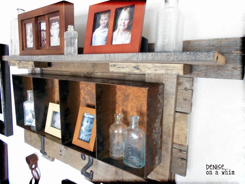 A pallet wood backer holds a rusty bin shelf via http://deniseonawhim.blogspot.com