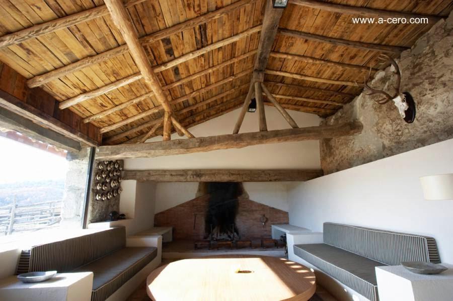 Ambiente con hogar de leños y techo rústico en madera