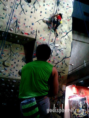 Indoor Wall Climbing - Two people working together to reach the top