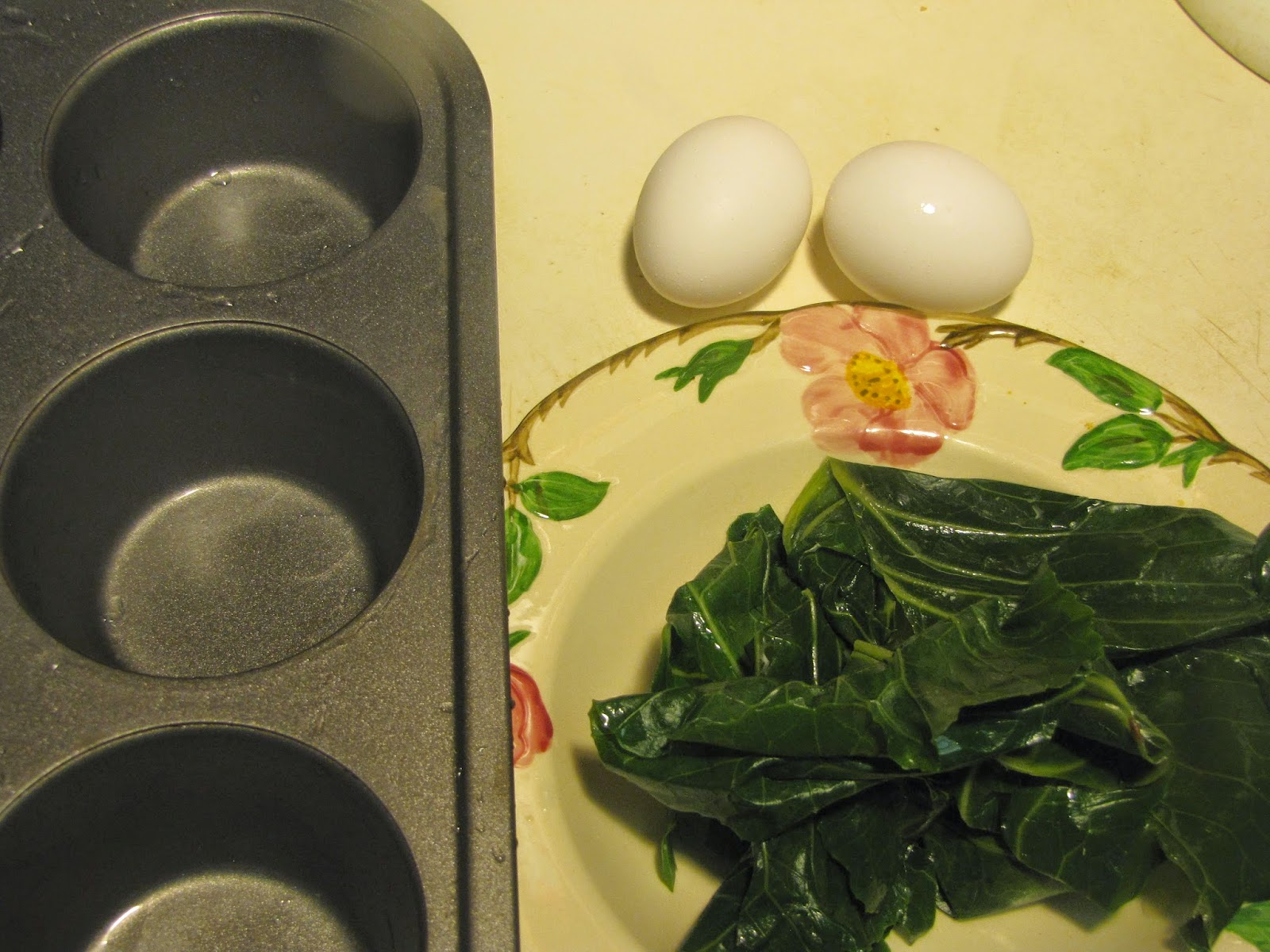 Cupcake pan, collard leaves and a couple of eggs