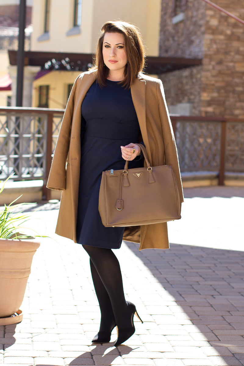camel coat, navy dress, black d'orsay pumps, tan prada bag