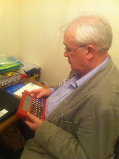 A picture of my Dad looking bankly at my red home calculator