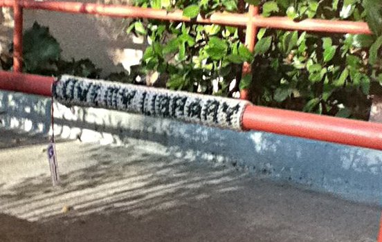 "Yarn bombing tag: ""LOVE MY LIBRARY"" attached to railing"