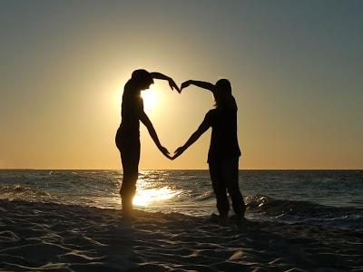 Dos enamorados forman un corazón en la playa