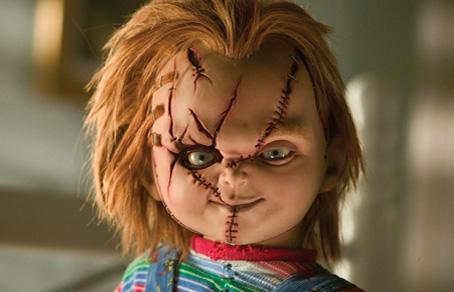 """Cette photo est celle de Chucky, la poupee possedee par le tueur en serie Charles Lee Ray qui est le personnage principal d'une serie de films d'horreurs realises entre 1988 et 2013. Cette image montre le visage connu de la poupee, avce ses cheveux roux hirsute, son regard bleu et demoniaque, son rictus méchant. La photo est certainement extraite d'un des derniers films puisque Chucky y apparait la face toute couturee, plusieurs cicatrices parcourant son visage en des diagonales plus ou moins longues et d'un rouge fonce. Cette image illustre a merveille le poeme """"Sale gosse"""" du Margina Magnifique qui revendique le fait de vouloir etre insouciant et terrible comme les enfants, plutot que de devenir un adulte range, sage et formate qui va au boulot tous les jours tel un robot ou un fantome. Un pome recreatif et intelligent de l'immense poete qu'est Le Marginal Magnifique !"""