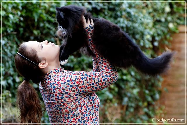 woman in orla kiely uniqlo top holding cat kissing kitten