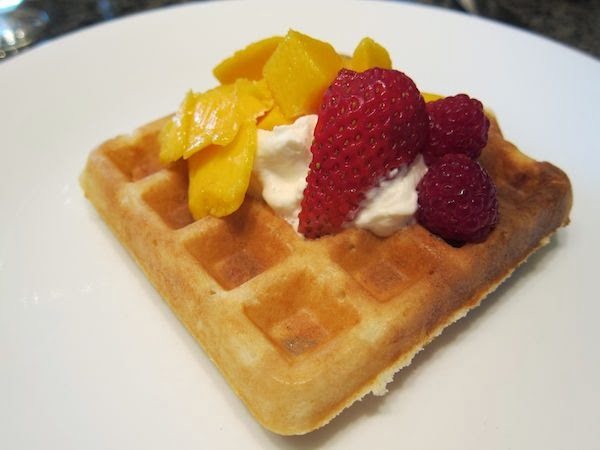Waffle wiith whipped cream, mango and strawberries