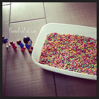 Playmobil figures lined up for the rainbow barley grains sensory play tub