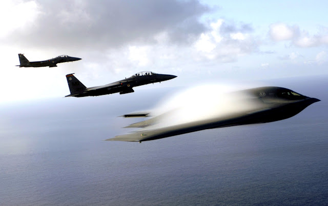 A B-2 Spirit and F-15E Strike Eagles fly in formation across the Pacific Ocean