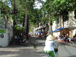 Woman on bicycle with Vietnamese hat. Ho Chi Minh City (Saigon)