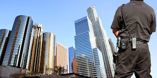Officer stands watch over city buildings.