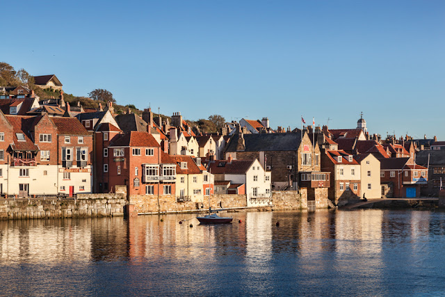 Reflection of houses in warm evening light in Whitby harbour North Yorkshire by Martyn Ferry Photography