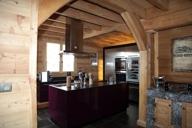 Cuisine design violette et inox avec îlot et meubles suspendus.