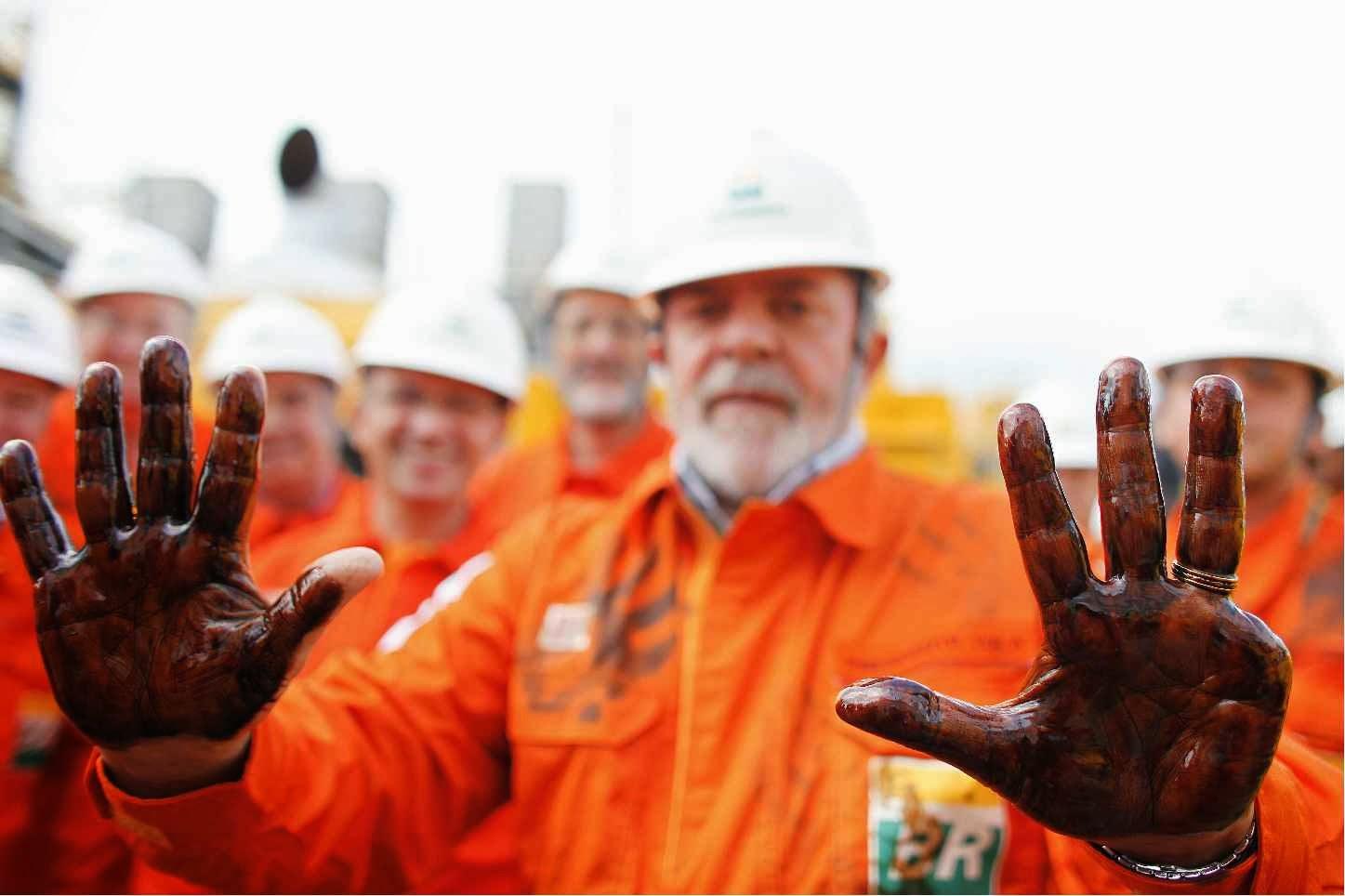 O ex-presidente Lula mostra as mãos sujas com petróleo da primeira extração feita pela Petrobras em 2008, na plataforma P-34, no campo de Baleia Franca, em Vitória (ES).