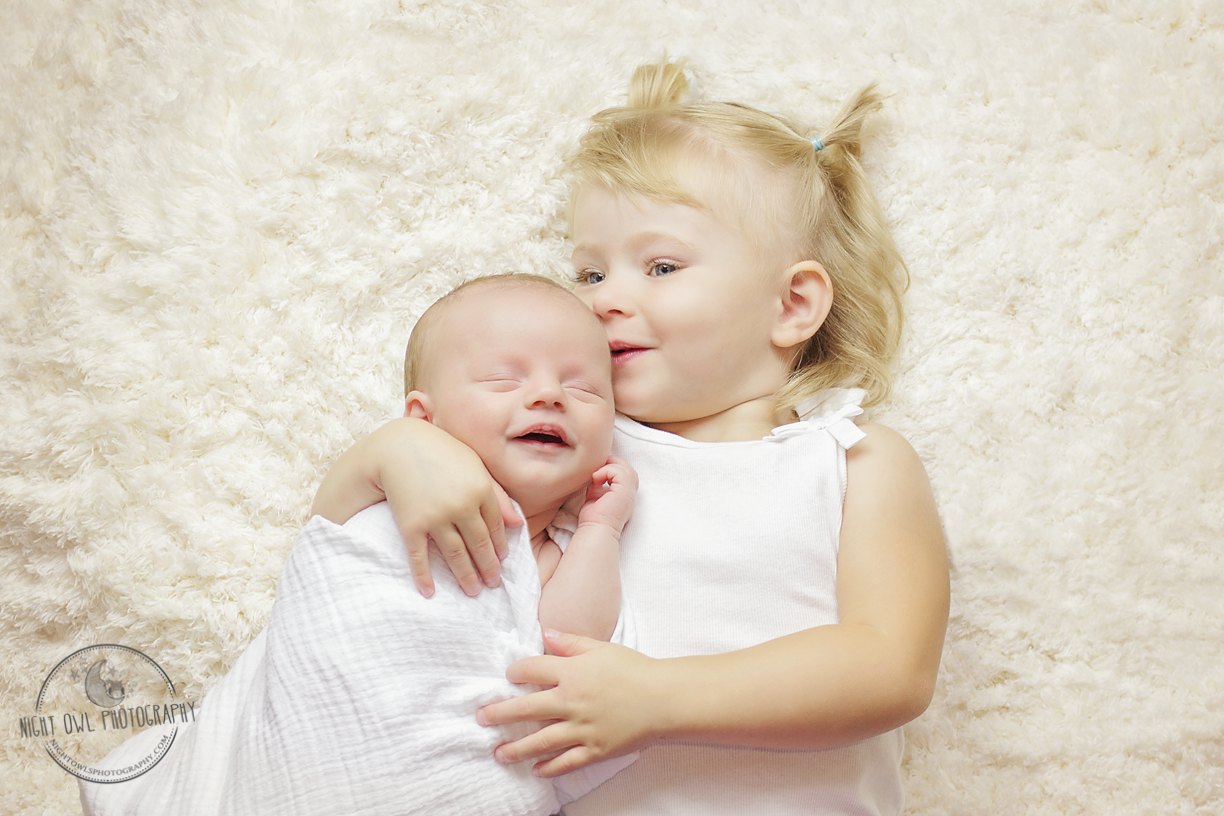 Smiling Newborn in Big Sisters arms ©nightowlsphotography.com