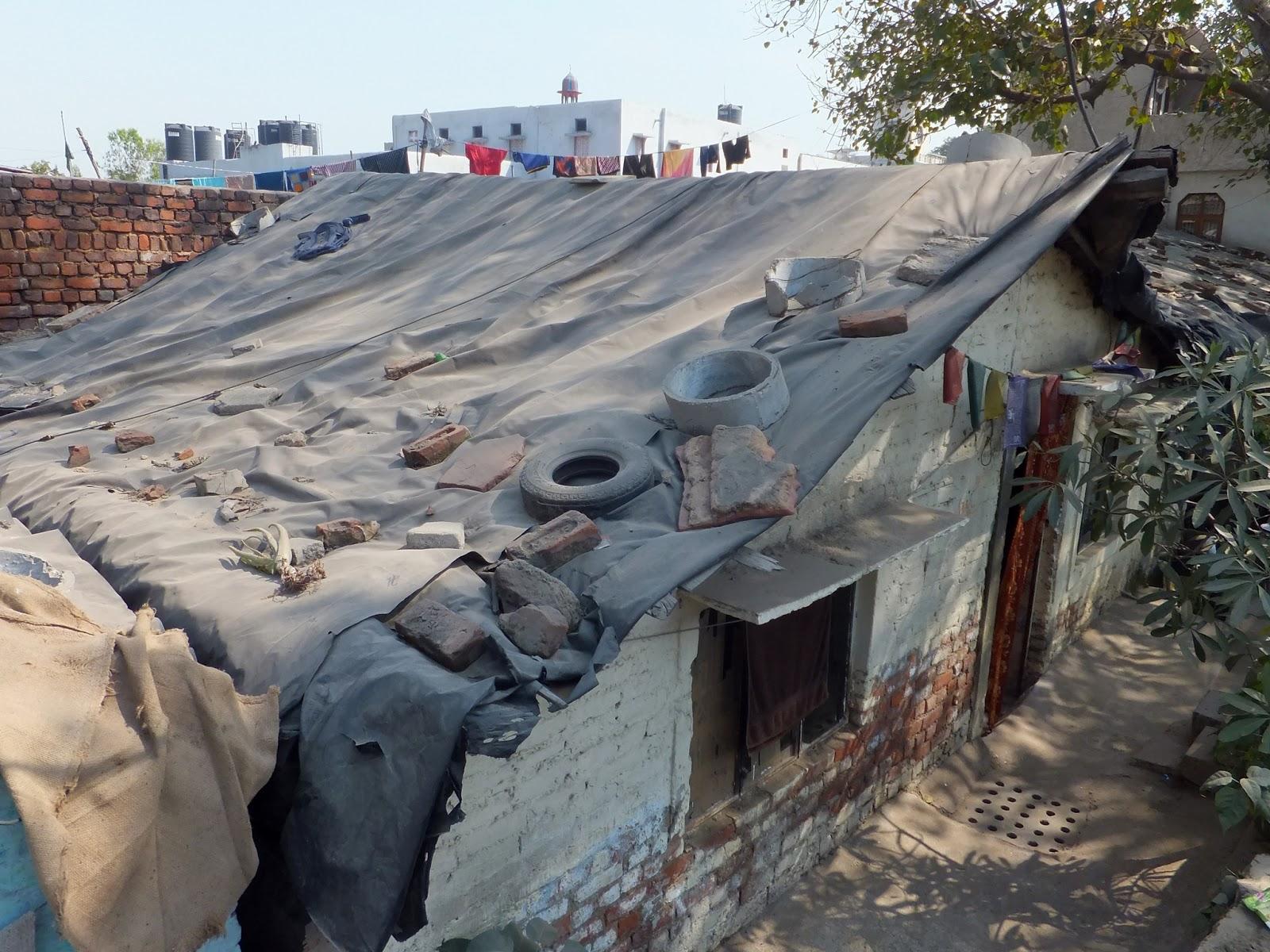 крыша покрытая брезентом и заваленная тротуарной мусором и шинами