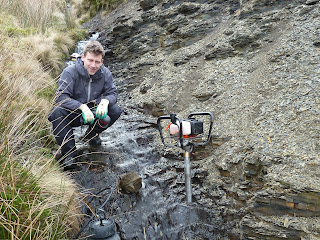 Joe in the field acquiring Bowland Shale samples from outcrop with the help of a hand-held core drill.