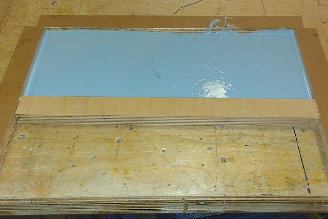 "A rectangular box of about 5"" by 9"" sits on a wooden table.  In the box is the blue mold making material.  It is over a piece of plastic with the desired Braille for the exhibit text and will create the mold for the cast of the exhibit text that will go on display."