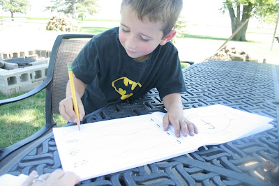 Boy doing workbook outside on picnic table: STEM mom