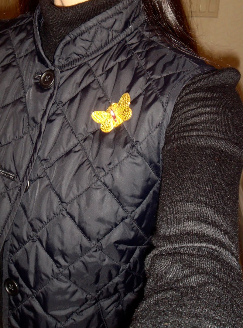 Close up of vintage gold butterfly brooch pinned on the quilted vest.