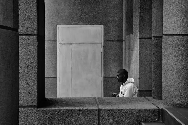 A man sits framed by concrete with a closed door behind him.