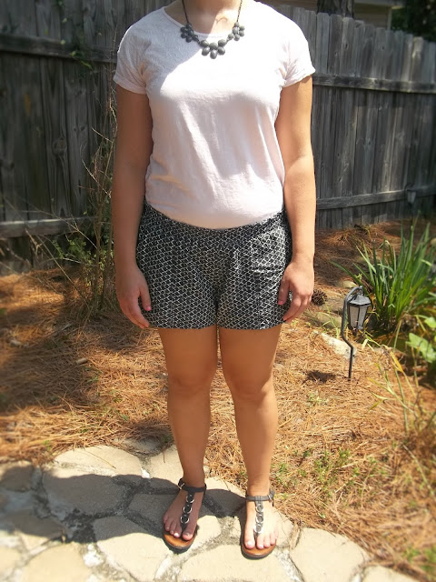 Pink lace tee, black and white patterned soft shorts, grey statement necklace, black sandals outfit outfit inspiration