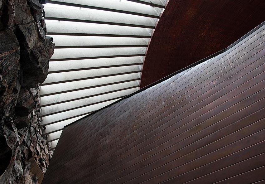 Foto sobre a clarabóia, com uma parede em primeiro plano e parede de granito à esquera. Imagem muito virda para o grafismo da conjugação dos elementos