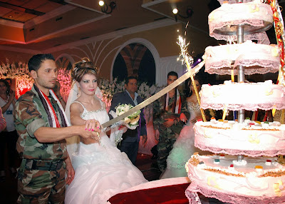 Syrian soldier and his bride cutting a wedding cake