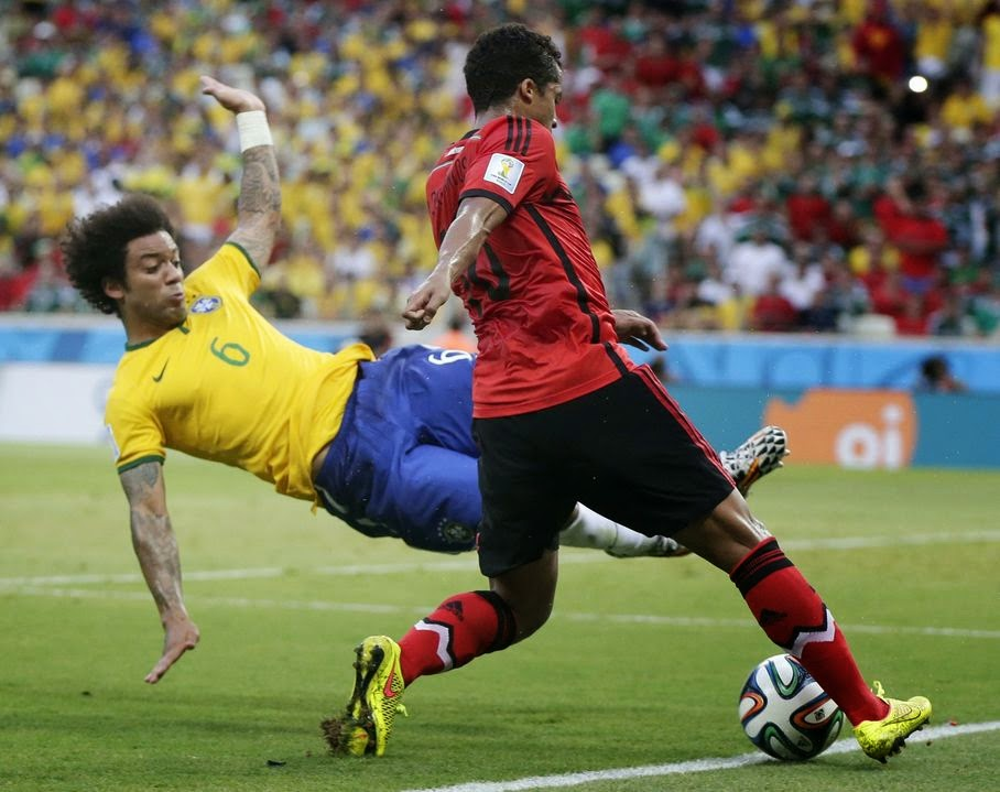 Brazil's Marcelo, left, dives to kick the ball away from Mexico's Giovani dos Santos during the group A World Cup soccer match between Brazil and Mexico at the Arena Castelao in Fortaleza, Brazil, Tuesday, June 17, 2014.