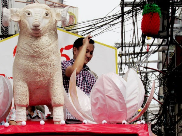 CHINATOWN: MMDA chairman Francis Tolentino beside an image of a sheep -- waves at the crowd