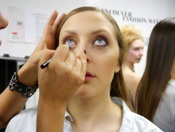 Vancouver Fashion Week Fall/Winter 2014 Martins Paulo show runway beauty look by Yasmin Morshedian. Morshedian applies eyeliner to the model's eyes' waterline.