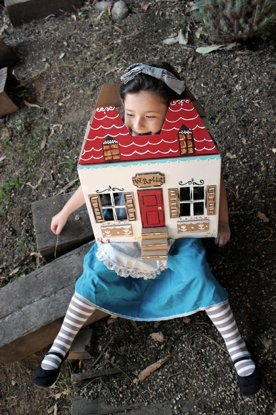 a little kid dressed as alice inside a paper house simulatin the giant effect on alice in wonderland