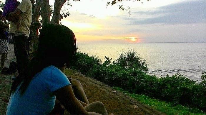 A girl looking at the sunset at Tanah Lot, Tabanan Bali Indonesia.