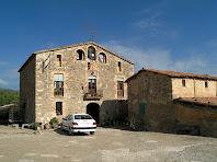 La façana principal de la masia de La Muntada i al seu davant, a la dreta, la masoveria
