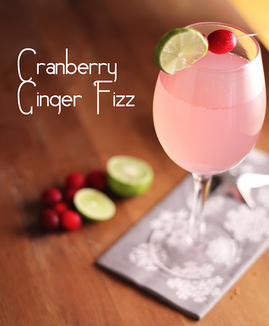 Cranberry Ginger Fizz in a wine glass with fresh cranberry and lime garnish