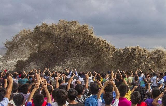 Туристы фотографируют волны, вызванные тайфуном «Усаги» в китайском городе Ханчжоу