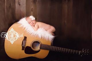Gambar bayi lucu tidur pulas di atas gitar
