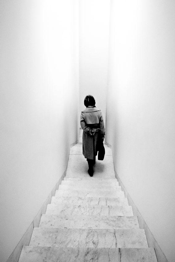 Escadaria entre paredes apertadas e lisas e uma mulher de costas a descer.