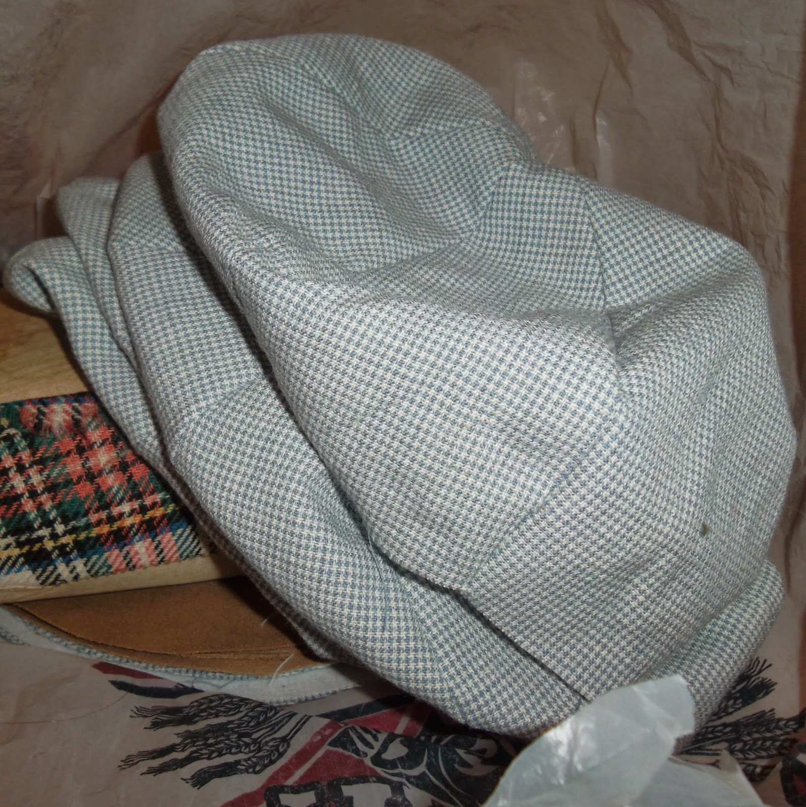 "Stack of assembled crowns for eight-panel ""newsboy"" hats in blue-and-white houndstooth fabric"