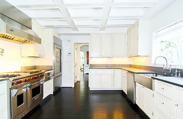 kitchen with a stainless wolf stove and oven, farmhouse sink, white cabinets and wood floor