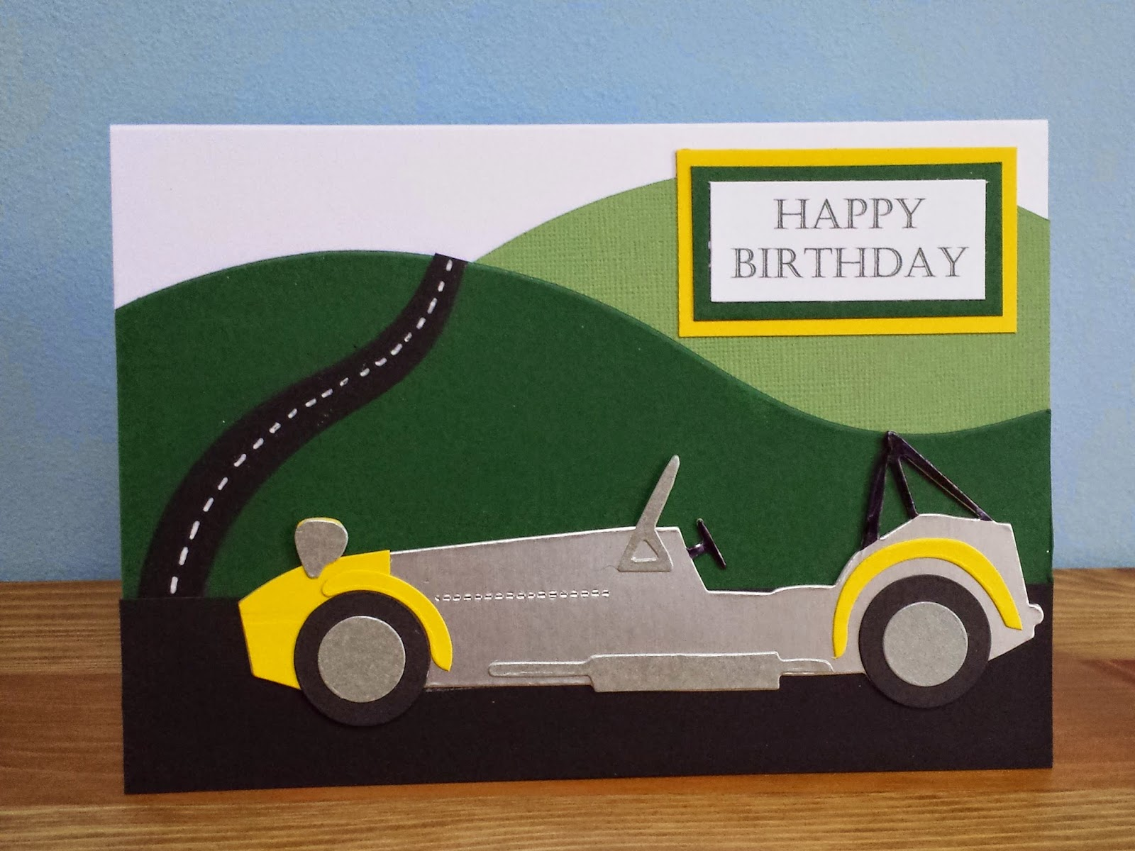 Happy Birthday Caterham card with aluminium look body panels and countryside background.