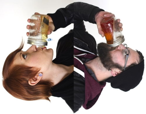man and woman drinking from ball jars