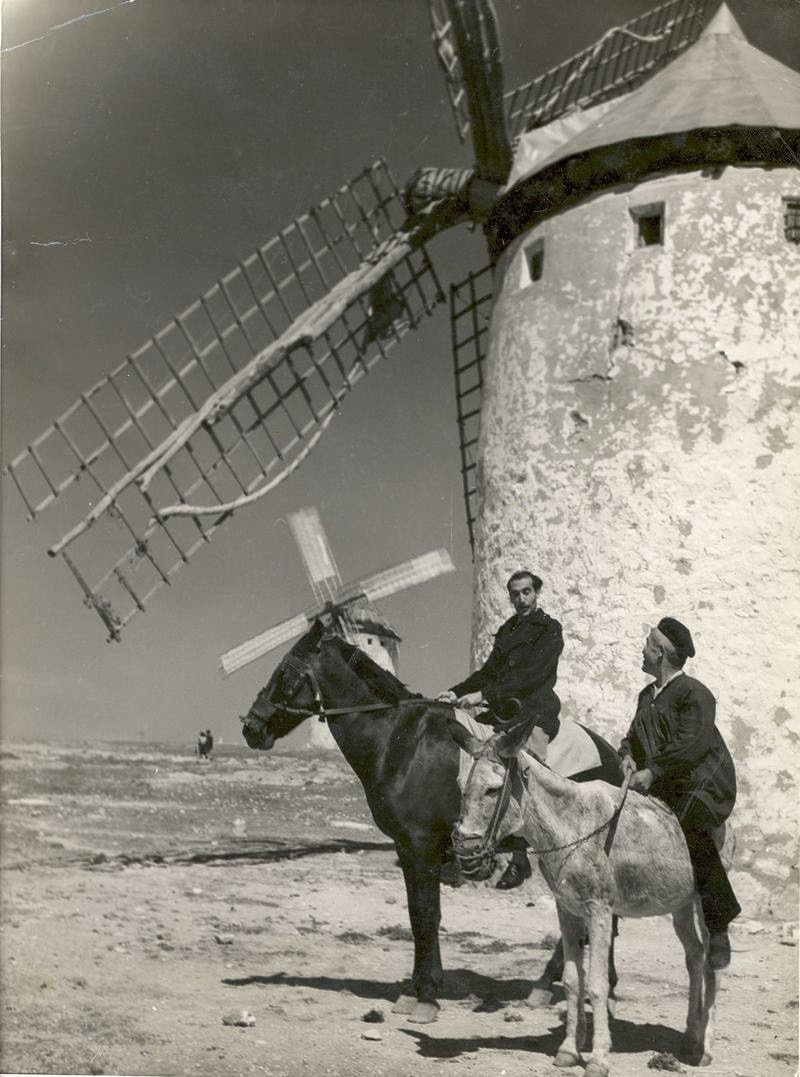 Image of two people riding a horse and a donkey with background about windmills of La Mancha.