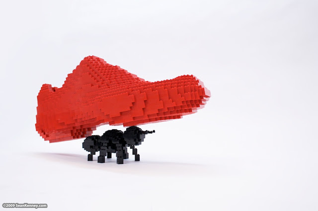 black Lego ant carrying a red Lego shoe
