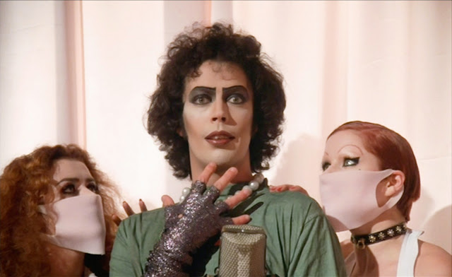 Left to right Patricia Quinn, Tim Curry, and Nell Campbell from The Rocky Horror Picture Show (1975). Tim Curry is wearing make-up and pearls and is dressed in operating room scrubs. He holds his right arm, covered in a sleeve of glittery fabric, up to his chin and stares out at the audience with a look of hopeful anticipation. Patricia Quinn and Nell Campbell are both looking up at him with their hands on his shoulders and wearing pink rubber surgical masks over their faces.