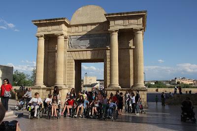 Conjunto de personas usuarias de sillas  de ruedas a su paso por el entorno de la Puerta del Puente recientemente remodelado.
